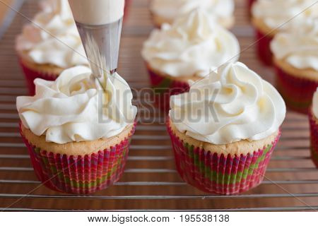 Handmade capcake with cream. Baker decorates muffins with cream and confectionery nozzles