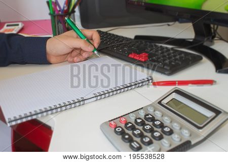 People calculate about and note data cost at home Finance managers taskConcept business and finance. Man hand with pen calculator and computer on wooden table