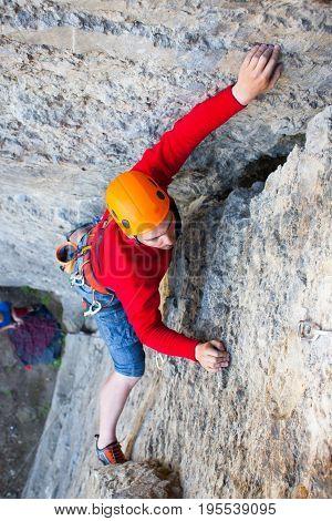 Climber In A Helmet Climbs Up.