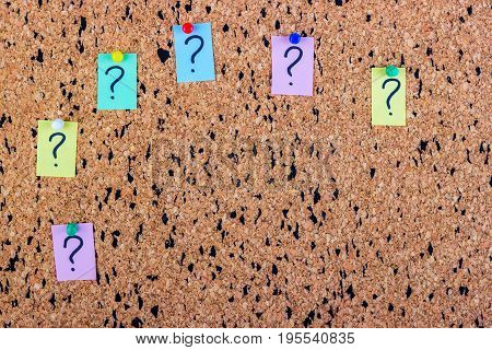uncertainty or doubt concept question mark on a sticky note on cork bulletin board
