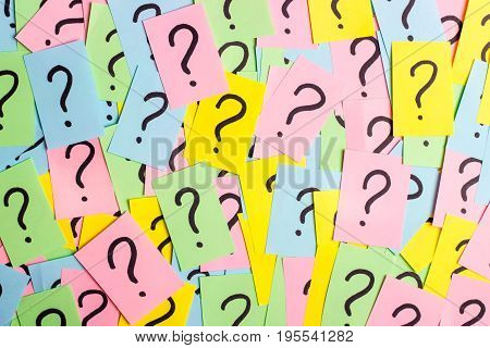 Too Many Questions. Pile of colorful paper notes with question marks. Closeup.