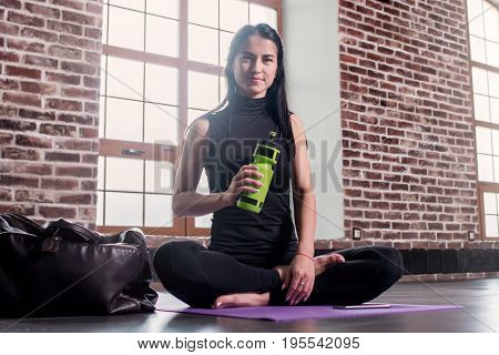 Portrait of young caucasian woman resting after training holding a sports bottle sitting on mat with legs crossed in gym with loft interior.