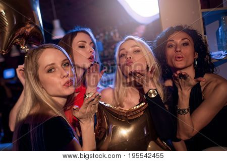 Group of attractive gorgeous girls blowing kisses looking at camera in nightclub.