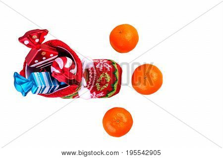 Red santa stocking with three decorative sweets inside and and three mandarins. Isolated on white background. Top view.