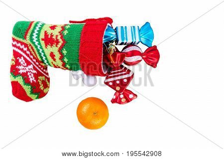 Red santa stocking with three decorative sweets inside and and mandarin. Isolated on white background. Top view.