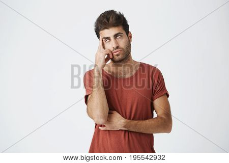 Trendy bearded young man tired of listening to somebody's stories or reproac s. Holding his head and rolling his eyes as he doesn't want to continue listening useless talks.