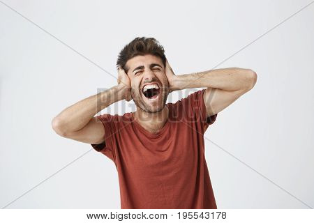 Young man with stylish hair covering his ears and shouting. Went into hysterics because of argument with his girlfriend or parents. Do not want to continue listening, opened his mouth in shriek expressing protest, disobedience.