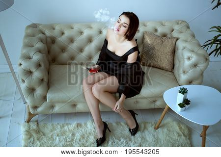 Beautiful woman smokes an e-cigarette while sitting on the couch.