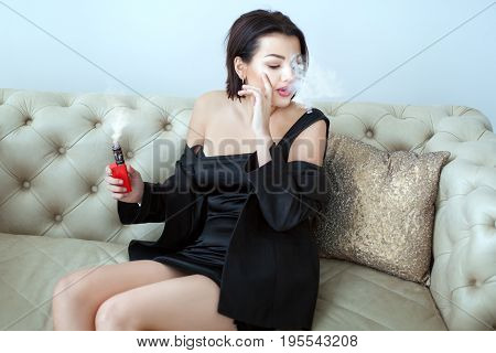 Young woman smokes an e-cigarette while sitting on the couch. She behaves defiantly. poster