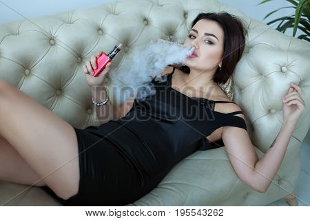 woman smokes a e-cigarette lying on the bed in the room. Smoker's concept Vaping