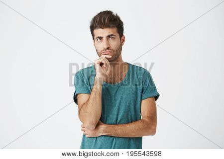 Fashionable, stylish man with dark eyes in casual clothes looking aside with placid and thoughtful look. Pensive guy with puzzled expression thinking about something or building plans.