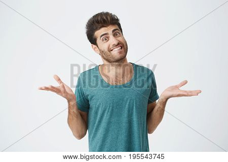Shot of attractive bearded grinning man dressed in blue T-shirt, telling he doesn t know what to do. Clueless and puzzled stylish student shrugging his shoulders expressing uncertainty. Facial expressions, life perception and attitude concept.