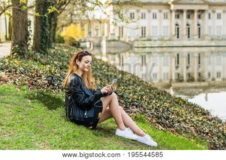 One woman listening music with earphones in the park near the water against the background of the building.