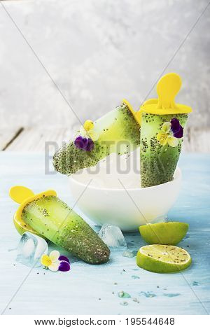 Magnificent homemade yellow-green fruit vegetarian lactose-free ice cream with chia seeds, fruit juice, limes with edible flowers and garden violas on a light background. Selective focus.