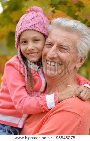 Happy grandfather and granddaughter in autumnal park