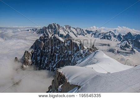 View of snowy peaks and mountaineers from the Aiguille du Midi, in French Alps Chamonix Mont Blanc, alpine mountains landscape, clear blue sky in warm sunny summer day