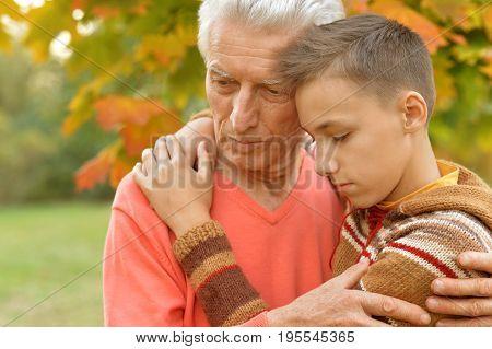 sad grandfather and grandson hugging  in park