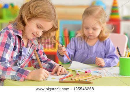 Cute little girls sitting at table and drawing with pencils in their room