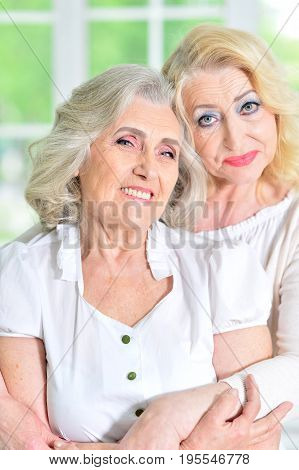 Close up portrait of mature woman hugging her mother