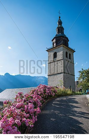 View of church steeple and flowers in the medieval village of Conflans, near the town of Albertville. Mountains landscape and blue sky on background. France