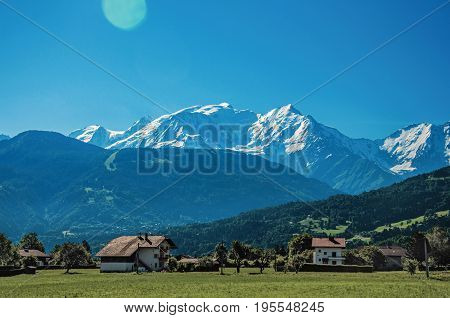Fields with houses, forest, alpine landscape and blue sky in the background, Saint-Gervais-Les-Bains, French Alps