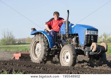 Man on a tractor with attached cutter