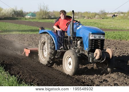 Tractor with a lowered cutter in the garden
