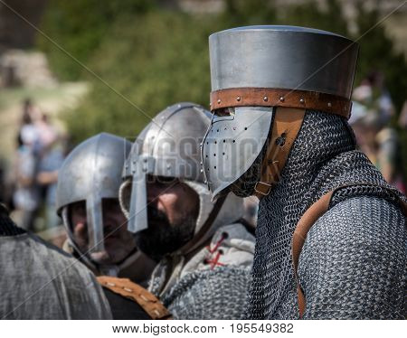 Medieval knight Isolated portrait with blurred background, reenactment with costumed characters and medieval armor with chainmail, helmet swords and shields. Medieval demonstration and recreation