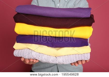Woman holding stack of clothes on color background. Combination of lilac and yellow colors