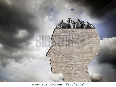 Head as wooden dustbin and black garbage bags. Garbage and pollution concept. Dramatic sky.