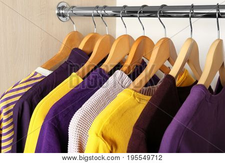 Wooden hangers with clothes in wardrobe. Combination of lilac and yellow colors