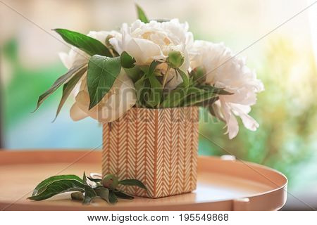 Beautiful bouquet with fragrant peonies on tray against blurred background