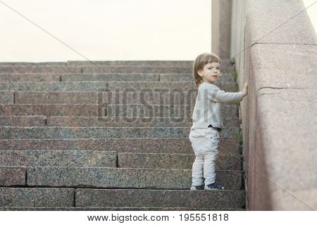 Little Blue-eyed Boy With Long Hair Standing In Front Of The Stone Stairs. The Concept Of Growing Up