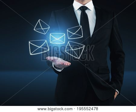 Businessman holding glowing digital letters on dark blue background. Email concept