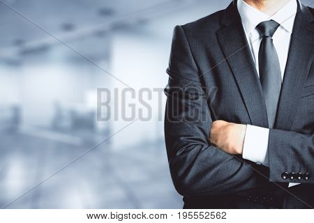 Businessman with folded amrs standing in blurry office interior. Copy space. Boss concept. 3D Rendering