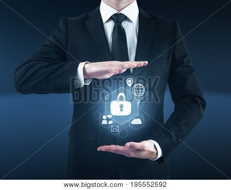Businessman holding abstract cybersecurity hologram in dark blue interior. Secure concept
