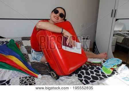 Happy young woman in colorful summer outfit near the red staffed suitcase. Young Girl packing suitcase on bed at home. Female with suitcase sitting on bed in hotel