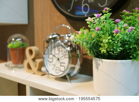 Bedhead decoration with plants and clock with selective focus