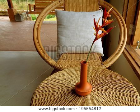 Relaxing space with rattan armchair and round table with Bird of Paradise flower in terracotta vase