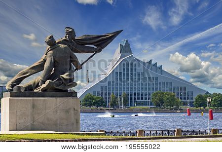 Embankment of Daugava river with old and modern architectural objects in center of Riga city - the capital of Latvia, major commercial, cultural, historical and financial center of the Baltic region