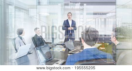 Successful team leader and business owner leading informal in-house business meeting. Businessman working on laptop in foreground. Business and entrepreneurship concept.