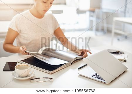Fashion design process. Woman working on laptop and skimming through a trendy catalog magazing to fight creative block after a caffeine overdose