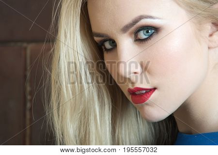 Girl with red lips on adorable face. Pretty woman fashionable model with blue eyes bright makeup and long blond hair posing on brown wall. Fashion make up visage and cosmetics. Beauty salon