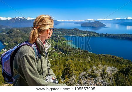 Woman sitting on the viewpoint on top of mount Cerro Campanario, Argentina and admiring the stunning views of Lake District