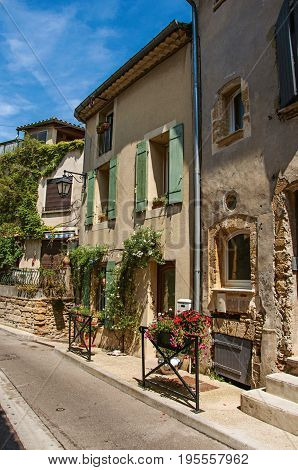 Street view with stone houses in the center of the village of Châteauneuf-du-Pape, blue sky and sunny day. Located in the Vaucluse department, Provence-Alpes-Côte d'Azur region in southeastern France