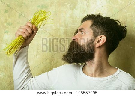 Hipster hold Italian macaroni. Cook or chef bearded man. Healthy food and dieting. Cooking raw spaghetti in restaurant. Man with pasta in hand.