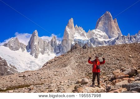 Male trekker standing on the rock in front of the stunning and impressive Mount Fitz Roy near El Chalten in Patagonia, Argentina