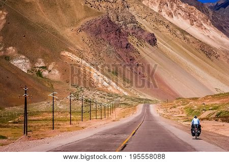 Woman cycling on the empty road from Mendoza in Argentina to Valparaiso in Chile, climbing constantly to the border and passing Park National Aconcagua on the way