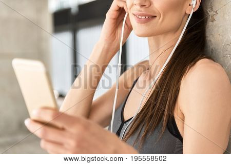 Close up of sincere smile of female athlete wearing earphones while enjoying music. She is standing and holding smartphone