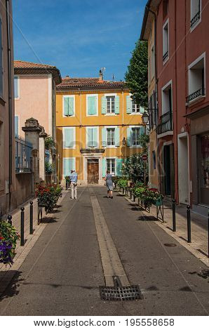 Orange, France, July 02, 2016. Two people on a street with colorful houses in the city center of historical Orange. Vaucluse department, Provence-Alpes-Côte d'Azur region, southeastern France